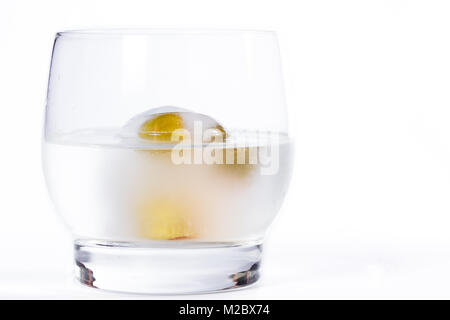 close up of a cocktail with a martini mixed and poured over a ice cube with frozen olives inside - Stock Photo
