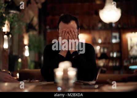 frustrated man in a restaurant - Stock Photo