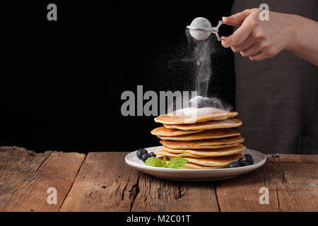 Stack of pancakes with sugar powder splashes cooking by chef hand on wooden dark background table. Copy space for - Stock Photo