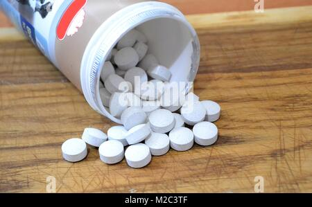 Pills scattered on the table out of the jar - Stock Photo