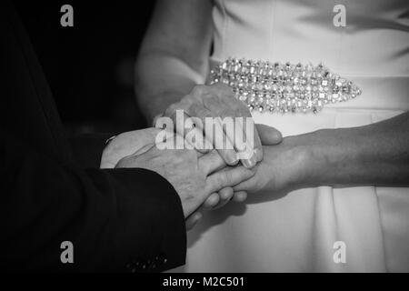 Bride and groom exchanging vows, holding hands, mid section, close-up, black and white