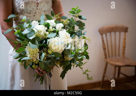 Bride holding wedding bouquet, mid section