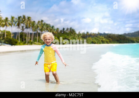 Child on beautiful beach. Little boy with toy boat running and jumping at sea shore. Ocean vacation with kid. Children - Stock Photo