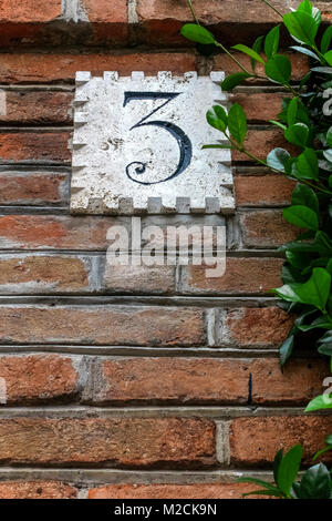 House number three, 3. In front of an ancient luxury residential apartment building in the Coppede quarter. Art - Stock Photo