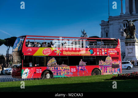 Tourist sightseeing, hop on hop off, red double decker bus, passing through Venice Square. Rome, Italy, Europe. - Stock Photo