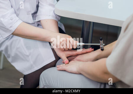 Cropped image of neurologist testing reflex on a female patient using a hammer - Stock Photo