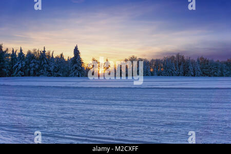 Sunset over the groomed cross country ski trails. Dramatic sky glowing by sunlight over the forest in background. - Stock Photo