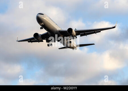 A WestJet Airlines Boeing 767-300ER aircraft on final approach to London Gatwick airport on a January morning - Stock Photo