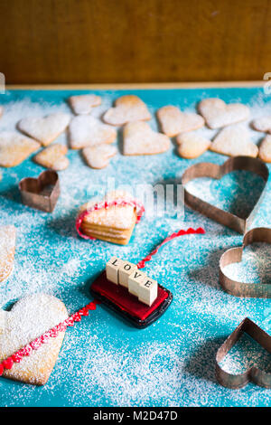 Baking Heart Shaped Cookies for valentine's day, with the words love created with colored stamps,  over an azul - Stock Photo