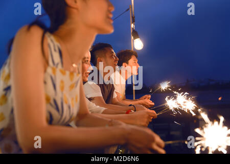 The young people gathered for fireworks - Stock Photo