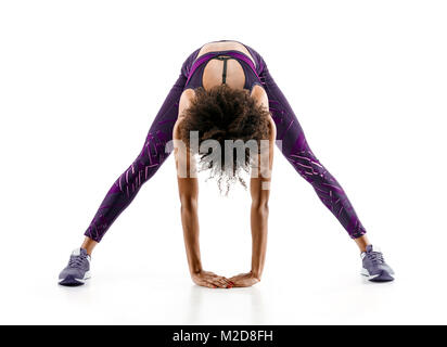 Fit girl warming up. Full length of young african girl in sportswear stretching her back on white background. Stretching - Stock Photo