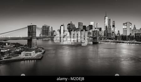 Sunrise on Lower Manhattan and the Brooklyn Bridge in Black & White. Financial District skyscrapers with East River. - Stock Photo