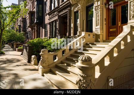 Brownstones with doorsteps and ornament in morning light. Upper West Side Street, Manhattan, New York City - Stock Photo