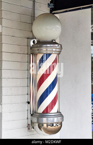 American barber pole on the exterior wall of a small town barber shop in Auburn Alabama, USA. - Stock Photo