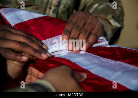 U.S. Army Soldiers, assigned to Bravo Company, 304th Expeditionary Signal Battalion, 1st Signal Brigade fold the - Stock Photo