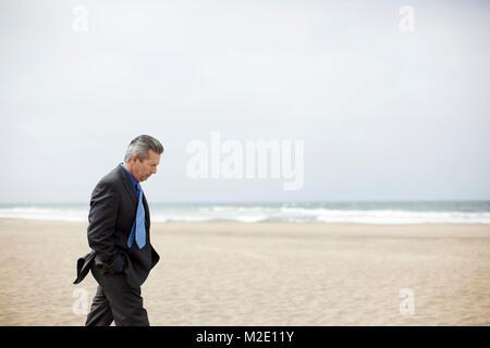 Pensive Hispanic businessman walking on beach - Stock Photo