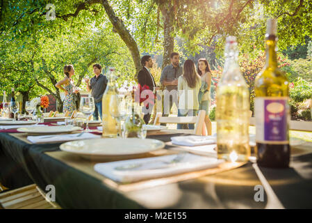 Wine bottles on table at party outdoors - Stock Photo