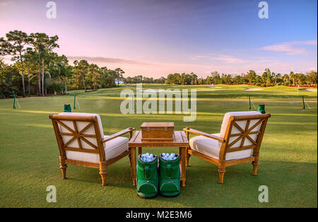 Chairs and golf balls on driving range - Stock Photo