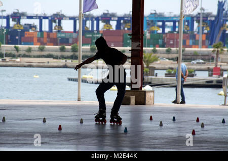 Skater Silhouettes at skate park in Valencia, Spain. Young & energetic rollerbladers enjoy the vigorous & technical - Stock Photo