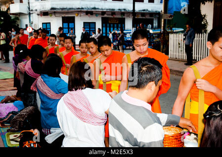 LUANG PRABANG, LAOS - February 16, 2011: Daily ritual of monks collecting alms and offerings - Stock Photo