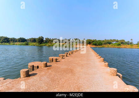 A river front with a very low height bridge across the river. Blue sky, blue water and green vegetation in form - Stock Photo