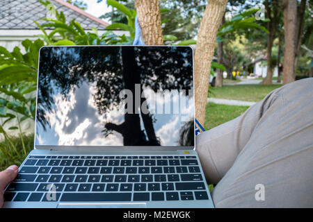 close up man in a hammock with laptop computer on vacation day relax time - Stock Photo