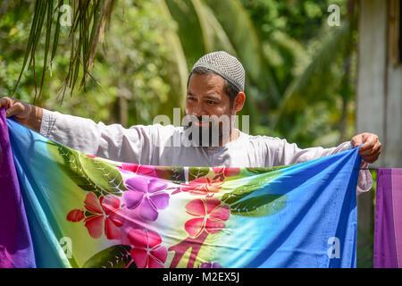 KRABI, THAILAND - MAY 2, 2015: Muslim man drying Batik fabric  outside home in Lanta island of Krabi, Thailand - Stock Photo