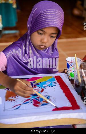 Krabi, Thailand - May 2, 2015: Muslim girl with purple hijab painting Batik fabric in Lanta island of Krabi, Thailand - Stock Photo