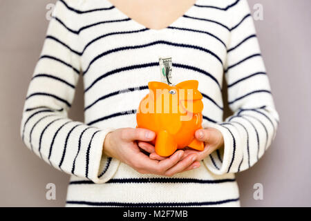 Young woman inserting dollar sign in orange piggy bank - Stock Photo