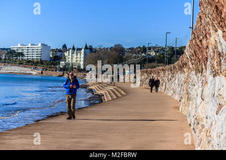 People walking along promenade by Torre Beach at high tide in February sunshine.  Just 2 degrees C but plenty of - Stock Photo