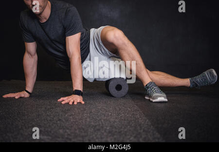 Athletic man using a foam roller to relieve sore muscles after a workout. - Stock Photo
