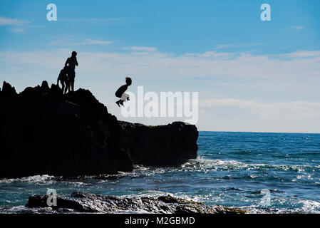 A silhouette image of a boy jumping from a rock into the ocean on an east coast Australian beach - Stock Photo