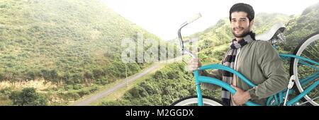 Travelling man with bicycle in front of landscape terrain - Stock Photo