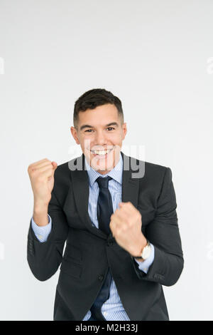Portrait of an excited, smiling, handsome, well dressed young man who is punching the air - Stock Photo