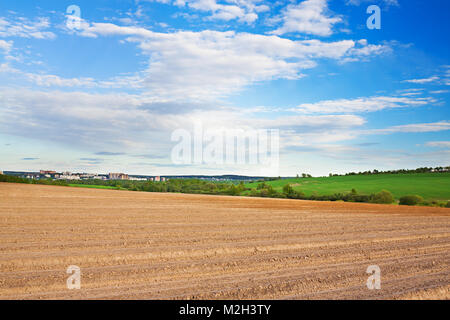 spring of landscape with ploughed field and blue sky with white clouds. agriculture farmland - Stock Photo