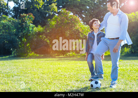 Loving father embracing son after playing football - Stock Photo