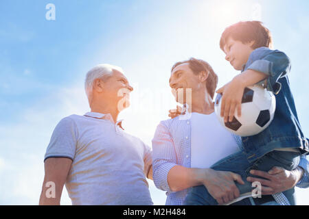 Three generations of men spending time outdoors - Stock Photo