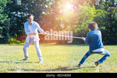 Excited father and son playing tug of war together - Stock Photo