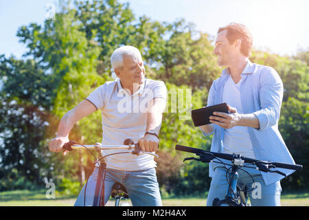 Father and son using touchpad while riding their bicycles - Stock Photo