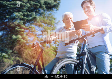 Senior dad and son smiling while looking at tablet computer - Stock Photo