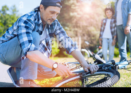Focused man trying to fix bike of his son - Stock Photo