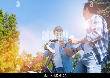 Harmonious family chatting during bicycle ride - Stock Photo