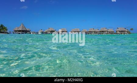 Tropical resort with thatched bungalows in the lagoon seen from sea surface, Tikehau atoll, Tuamotus, French Polynesia, - Stock Photo