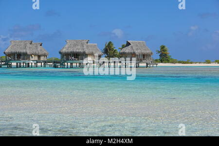 Tropical bungalows over water in the lagoon, Tikehau atoll, Tuamotus, French Polynesia, Pacific ocean, Oceania - Stock Photo