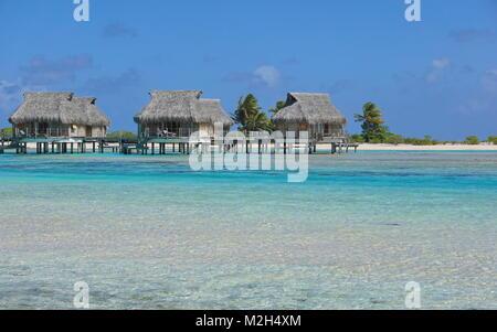 Tropical bungalows over water in the lagoon, Tikehau atoll, Tuamotus, French Polynesia, Pacific ocean, Oceania - Stock Photo