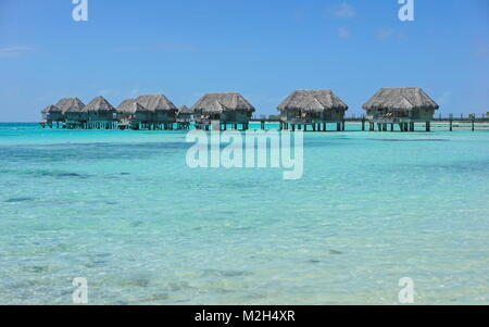 Tropical bungalows overwater in a lagoon with turquoise water, Tikehau atoll, Tuamotus, French Polynesia, Pacific - Stock Photo