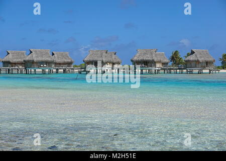 Tropical resort with overwater bungalows in the lagoon, Tikehau atoll, Tuamotus, French Polynesia, Pacific ocean, - Stock Photo