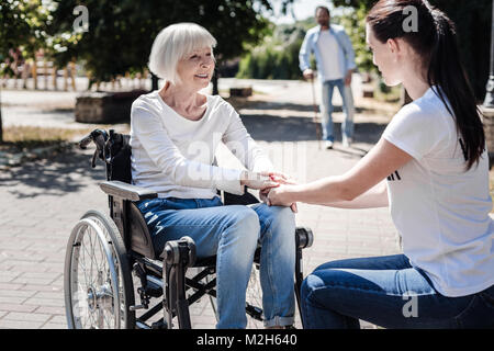 Joyful aged woman being thankful for support - Stock Photo