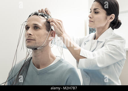 Professional female doctor putting electrodes - Stock Photo