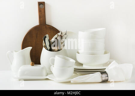 White tableware for serving. Crockery,dish, utensils and other different white stuff on white table-top. Kitchen - Stock Photo